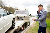 image of tow-truck  - Man calling while tow truck picking up his broken car  - JPG