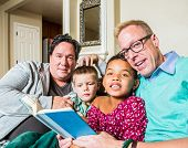 image of gay couple  - An attractive gay couple reads to their children in living room - JPG