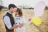 stock photo of in-love  - Young happy couple holding colorful balloons and embracing - JPG