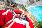 pic of sleeping bag  - Young couple lying in red sleeping bags near the sea - JPG