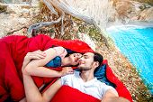 foto of sleeping bag  - Young couple lying in red sleeping bags near the sea - JPG