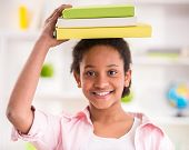 stock photo of mulatto  - Young smiling mulatto schoolgirl holding some books on her head - JPG