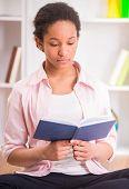 foto of mulatto  - Young pretty mulatto schoolgirl reading a book on colorful background - JPG