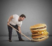 picture of bic  - Man lifts with shovel a giant sandwich - JPG