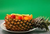 stock photo of green papaya salad  - Thai style fruit salad inside a pineapple with a green background - JPG