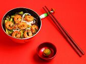 stock photo of shrimp  - Vietnamese shrimp and rice noodles soup pho on a red background - JPG