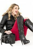 pic of woman boots  - portrait of sitting woman wearing fashionable clothes and boots with a handbag - JPG