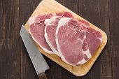pic of pork chop  - Raw pork chop steak and cleaver on wooden background - JPG