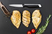 foto of cutting board  - Ready chicken  fillet on the old plastic cutting board - JPG