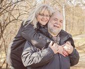 picture of piggyback ride  - Happy Senior Man giving Mature Woman Piggyback ride outdoors - JPG