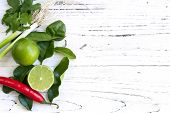Постер, плакат: Kaffir lime leaves fruit coriander or cilantro red chilli and green onions over white distressed