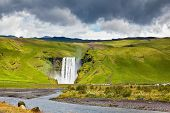 stock photo of waterfalls  - Huge picturesque waterfall and creek running along the road - JPG