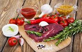 stock photo of beef shank  - Fresh beef steak with spices vegetables and sauce on a wooden background - JPG