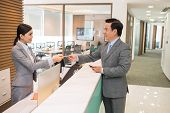 picture of receptionist  - Beautiful receptionist giving smart card to the businessman - JPG