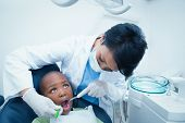 picture of dentist  - Female dentist examining boys teeth in the dentists chair - JPG