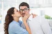 stock photo of office romance  - Businesswoman kissing her handsome colleague in the office - JPG