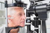 stock photo of slit  - Senior man looking into slit lamp at clinic - JPG