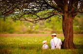 Father And Son Sitting Under The Tree On Spring Lawn poster