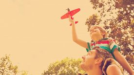 image of aeroplan  - Low angle view of a boy with toy aeroplane sitting on fathers shoulders at the park - JPG