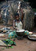 The Baka  Woman Pounds A Flour In A Mortar.
