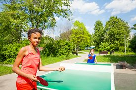 image of ping pong  - Two girls playing ping pong outside during summer sunny day - JPG