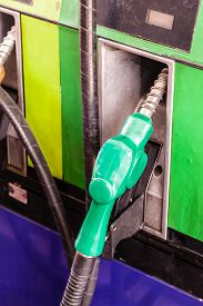 stock photo of petrol  - colored petrol gas pump nozzles in a service station - JPG