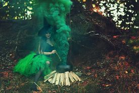 stock photo of cauldron  - woman witch in the forest preparing a potion in a cauldron on nature - JPG