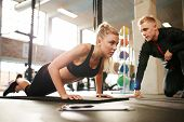 Trainer Helping Woman Do Push Ups poster