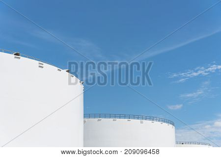 poster of Oil tanks in a row under blue sky in Pasadena, Texas, USA. Large white industrial tank for petrol, oil, natural gas storage. Tank farm at petrochemical, oil refinery plant. Energy and power background
