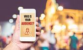 Hand Holding Mobile With Who Is Your Audience? Word On Screen With Blur Crowd Of People At Market Ba poster