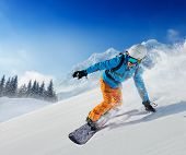 Young man snowboarder running down the slope in Alpine mountains. Winter sport and recreation, leisu poster