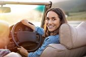 Happy woman holding steering wheel ready to drive and looking back. Smiling mature woman driving con poster