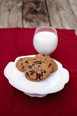 Chocolate chip cookies on a white plate with whole milk in a glass on a red tablecloth