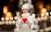 love, charity, holidays and people concept - happy girl in winter clothes with red heart over christ poster