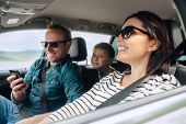 Happy Family Auto Traveling Concept Image. Car Interior View Of Female Driving, Man Dealing Mobile P poster