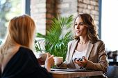 Two Young Business Woman Sitting At A Table In A Cafe. Girls Communicate And Discuss Matters. Friend poster