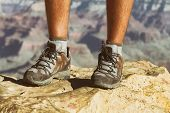 Mountain hike man hiker trekking travel walking with hiking shoes closeup of feet standing on rock. poster