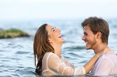 Side View Portrait Of A Happy Spontaneous Couple Joking In The Water On The Beach poster