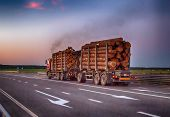 A Loaded Timber Truck Transports Timber Logs With An Overload On The Highway, Black Smoke. The Conce poster