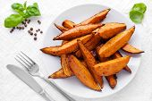 stock photo of batata  - Delicious homemade sweet potato wedges on a plate - JPG