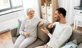 family, generation and people concept - happy smiling senior mother talking to adult son at home poster