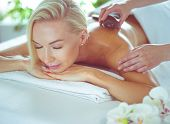 Young woman getting hot stone massage in spa salon. Beauty treatment concept poster