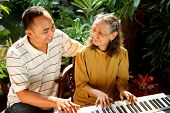 Ethnic Elderly Mother And Son Happy Playing Piano