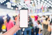 Mobile Phone Mockup Image, Hand Holding Blank Screen Mobile Smart Phone With Blurred  Crowd Of Peopl poster