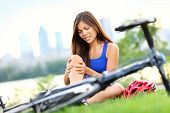 Knee pain bike injury. Woman with pain in knee joints after biking on bicycle. Girl sitting down wit