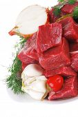 raw fresh beef meat slices in a white bowls with onion and red peppers isolated over white background