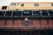Bluesman With Acoustic Guitar On Railroad Bridge. Cool Guy Plays Guitar Near Running Train. Showy Pe poster