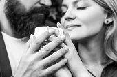 Couple Enjoying Coffe. Lovely Couple Holding Cup Of Coffe In Hands. Bearded Man Hugs Girl. Female An poster