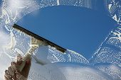 stock photo of window washing  - Window cleaner using a squeegee to wash a window - JPG