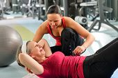 stock photo of personal assistant  - Fitness center senior woman exercise with personal trainer on mat - JPG
